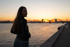 Den unga kvinnan som tycker om en solnedgång, promenerar floddaugavaen med en sikt över klar blå himmel royaltyfria bilder