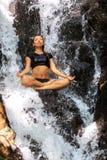 Den unga kvinnan som tycker om i yoga, poserar i vattenfall Royaltyfri Bild