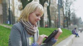 Den unga kvinnan som vilar i parkera, tycker om en digital minnestavla lager videofilmer