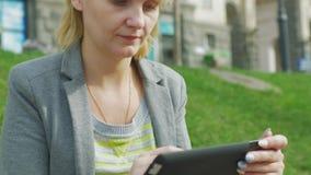 Den unga kvinnan som vilar i parkera, tycker om en digital minnestavla arkivfilmer