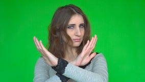 Den unga kvinnan som visar ett stopp, beväpnar korsat, medan se kameran över grön bakgrund lager videofilmer