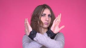 Den unga kvinnan som visar ett stopp, beväpnar korsat, medan se kameran över rosa bakgrund lager videofilmer