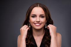 Den unga kvinnan som visar henne nya örhängen Arkivfoton