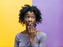 Den unga kvinnan som viskar en hemlighet bak hennes hand arkivfoto