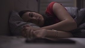 Den unga kvinnan sover i en mysig säng och därefter vaknar och startar att använda hennes mobil enhet arkivfilmer