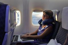 Den unga kvinnan sover i flygplan under flyget Arkivbild