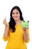 Den unga kvinnan sparar pengar i spargrisen Arkivfoto