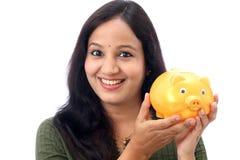 Den unga kvinnan sparar pengar i spargrisen Royaltyfri Bild