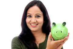 Den unga kvinnan sparar pengar i spargrisen Royaltyfri Foto