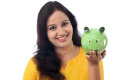 Den unga kvinnan sparar pengar i spargrisen Royaltyfria Bilder