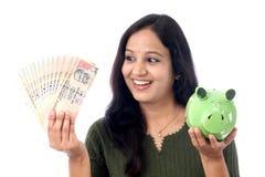 Den unga kvinnan sparar pengar i spargrisen Royaltyfria Foton