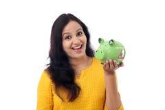 Den unga kvinnan sparar pengar i spargrisen Arkivbild