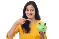 Den unga kvinnan sparar pengar i spargrisen Arkivbilder