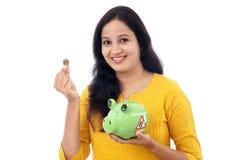 Den unga kvinnan sparar pengar i spargrisen Fotografering för Bildbyråer