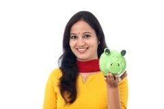 Den unga kvinnan sparar pengar i spargrisen Royaltyfri Fotografi