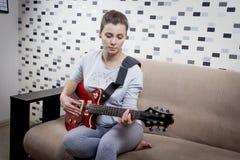 Den unga kvinnan spelar den elektriska gitarren hemma Flickan är musikern Royaltyfri Fotografi