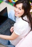 Den unga kvinnan spelar på bärbara datorn Royaltyfri Foto