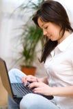 Den unga kvinnan spelar på bärbara datorn Arkivfoto