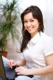 Den unga kvinnan spelar på bärbara datorn Royaltyfria Foton