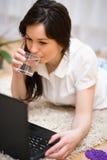 Den unga kvinnan spelar på bärbara datorn Arkivfoton