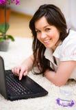 Den unga kvinnan spelar på bärbara datorn Royaltyfri Fotografi