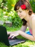 Den unga kvinnan spelar på bärbara datorn Fotografering för Bildbyråer