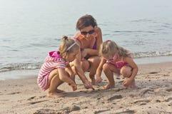 Den unga kvinnan spelar på stranden med två små flickor Arkivfoton