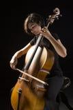 Den unga kvinnan spelar violoncellen Arkivbild
