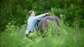 Den unga kvinnan ställer in sadeln på hästen i ängen lager videofilmer