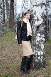 Den unga kvinnan står i trän bredvid björkträd Arkivfoton