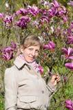 Den unga kvinnan står nära den blomstra liljamagnolian royaltyfri bild
