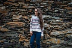 Den unga kvinnan står på bakgrund av stenar fotografering för bildbyråer