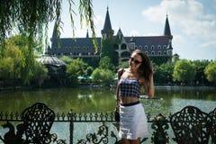 Den unga kvinnan står på bakgrunden av den härliga groteska slotten Arkivbild