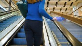 Den unga kvinnan står på rulltrappan i gallerian stock video