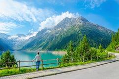 Den unga kvinnan står vid bergsjön, Österrike Arkivfoto