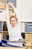 Den unga kvinnan sträcker armar i kontoret royaltyfria foton