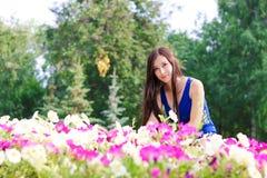Den unga kvinnan, student, sitter nära blommorna i parkera Arkivfoto
