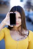 Den unga kvinnan täcker hennes framsidaskärmsmartphone arkivfoton