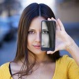 Den unga kvinnan täcker hennes framsidaskärmsmartphone royaltyfria foton