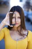 Den unga kvinnan täcker hennes framsidaskärmsmartphone royaltyfria bilder