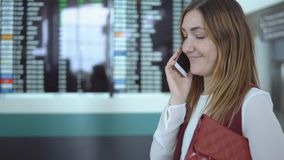 Den unga kvinnan talar på smartphonen på bakgrunden av det oskarpa funktionskortet med meddelandet arkivfilmer