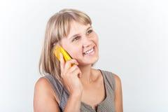 Den unga kvinnan talar på telefonen Arkivfoto