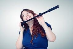 Den unga kvinnan talar på telefonen med en pinnesjälv Royaltyfri Foto