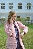 Den unga kvinnan talar vid mobiltelefonen och blickarna på klockan fotografering för bildbyråer