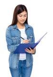 Den unga kvinnan tar anmärkningen på skrivplattan Arkivfoto