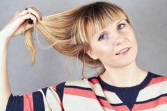 Den unga kvinnan tar av en hårmusikband från hennes hår Royaltyfri Fotografi