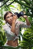 den unga kvinnan tar bilden i djungeln royaltyfri bild