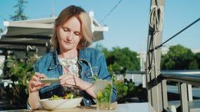 Den unga kvinnan tar bilder av härlig disk i ett kafé Godan vilar på sommarverandan och sommarsemestern stock video