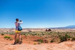 Den unga kvinnan tar bilder på monumentdalen Arkivbilder