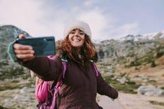 Den unga kvinnan tar ett fotografi på berget royaltyfri foto